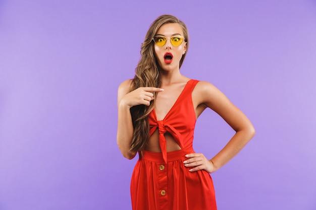 Glamour jovem mulher usando vestido vermelho e óculos de sol pensando ou expressando surpresa