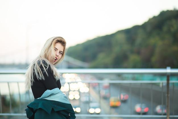 Glamour jovem vestindo casaco verde posando na ponte com luzes. espaço para texto