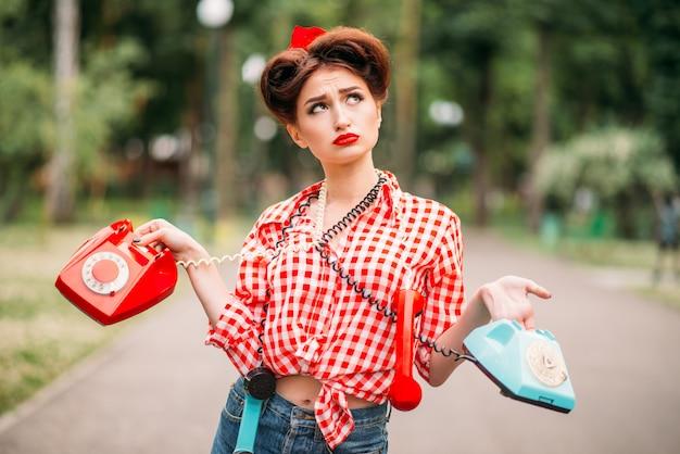 Glamour pin up girl com telefones rotativos retrô, moda americana vintage. mulher atraente no estilo pinup