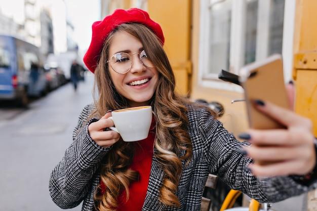 Glamourosa garota pálida de óculos fazendo selfie enquanto bebe café em uma cafeteria ao ar livre