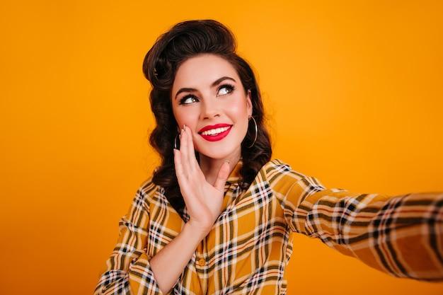Glamourosa jovem de camisa quadriculada tomando selfie. foto de estúdio da incrível garota pin-up isolada em fundo amarelo.