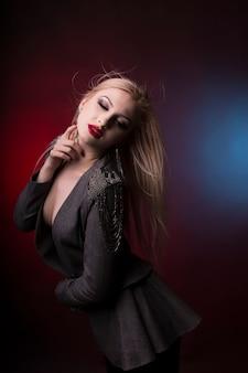 Glamourosa jovem loira com cabelo em movimento no estúdio