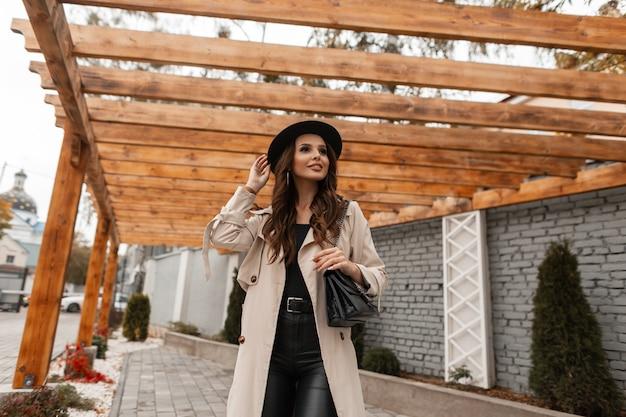 Glamourosa linda jovem feliz com um sorriso fofo em roupas da moda: casaco bege clássico, chapéu com bolsa de couro anda na rua na cidade