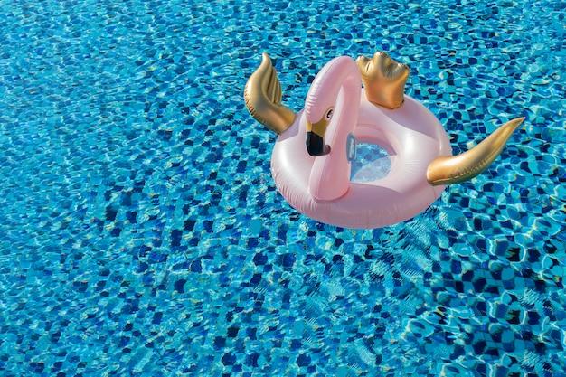 Glamourosa rosa e ouro cisne flamingo piscina flutuam na piscina azul com copyspace