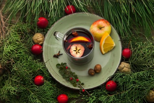 Glintwine em um copo de bebida alcoólica quente caseira para feriados com ramos de abeto