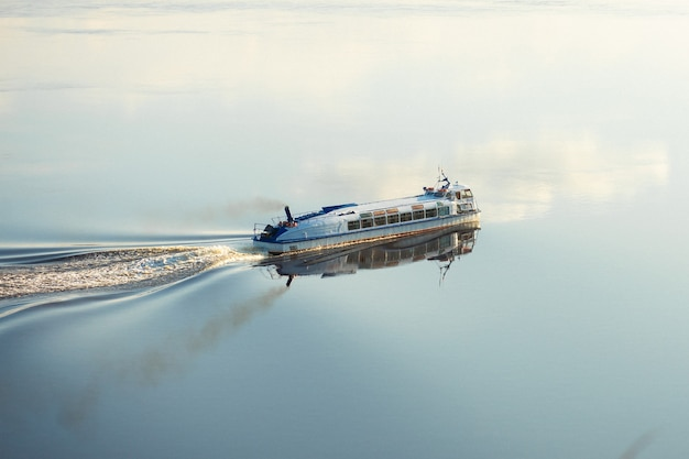 Glisser de navio fluvial de alta velocidade de passageiros navega ao longo do rio em direção ao pôr do sol.