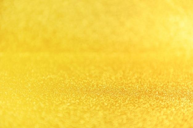 Glitter dourado fechar fundo. cenário desfocado amarelo cintilante.