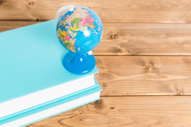 Globo colorido em livros azuis na mesa de madeira