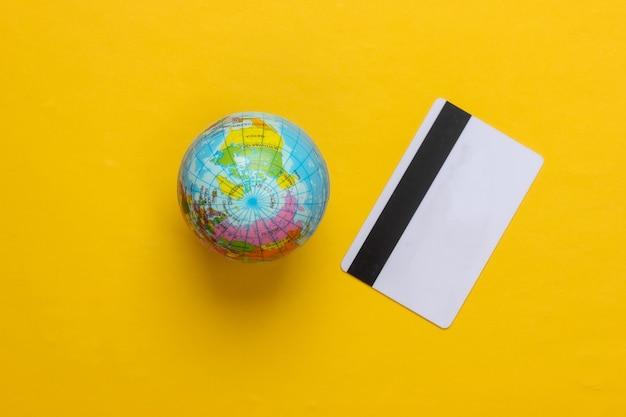 Globo com um cartão de crédito em fundo amarelo. vista do topo. minimalismo