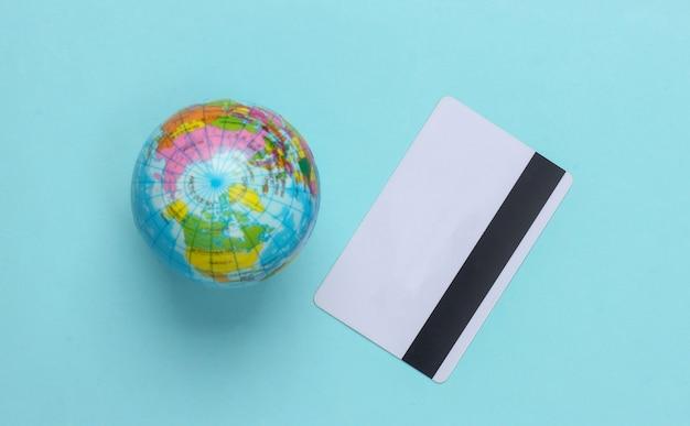 Globo com um cartão de crédito em uma superfície azul. vista do topo