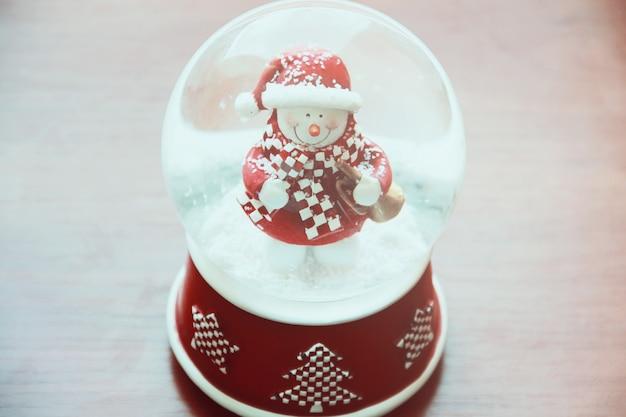 Globo de neve com boneco de neve na mesa de madeira