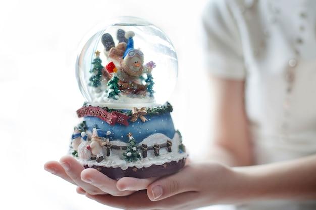 Globo de neve com um boneco de neve nas mãos de uma menina