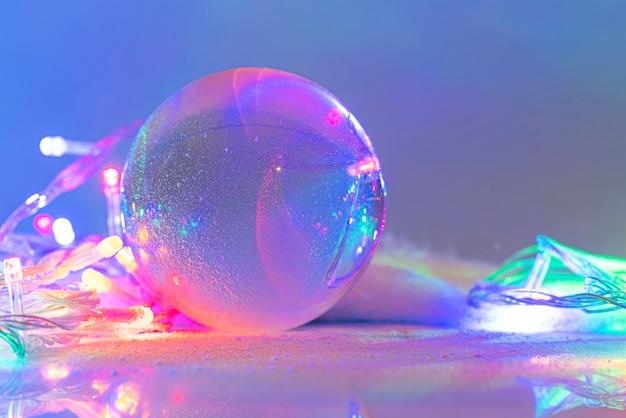 Globo de neve ou bola de vidro coberta pela neve com guirlanda, decoração de natal