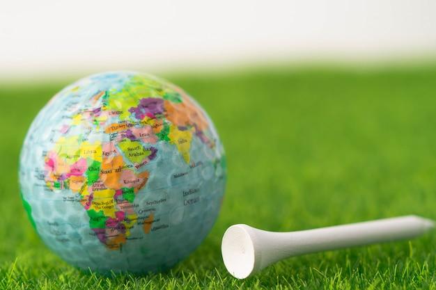 Globo do mundo em bola de golfe com tee na grama verde