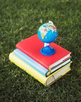 Globo do mundo pequeno na pilha de livros didáticos