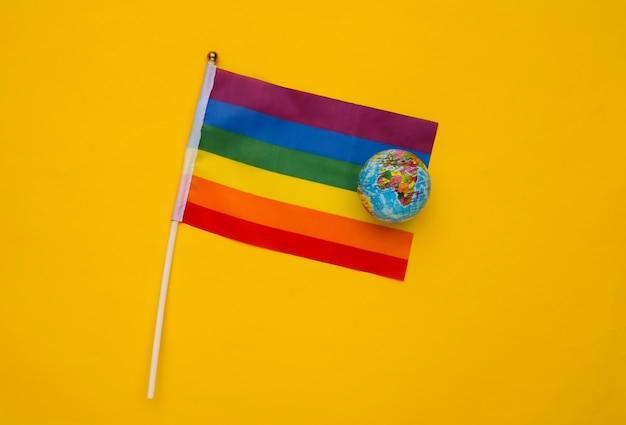 Globo e bandeira do arco-íris lgbt em fundo amarelo. parada gay, liberdade, tolerância