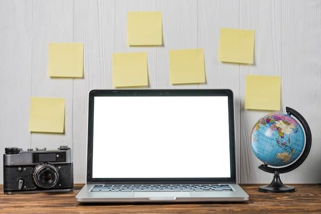 Globo e câmera perto de notas e laptop