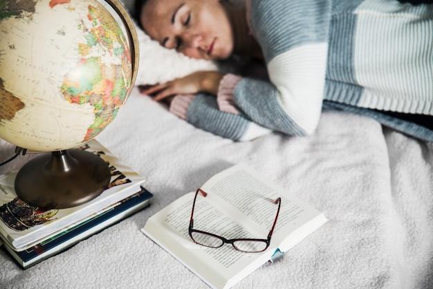 Globo e livros perto da mulher adormecida