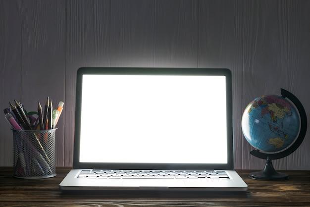 Globo e papelaria perto do laptop