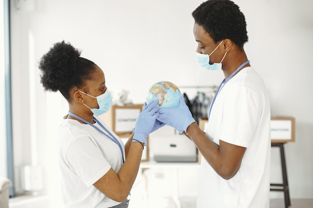Globo nas mãos. máscara de proteção e luvas. homens e mulheres africanos.