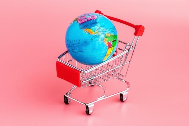 Globo pequeno em um carrinho de compras em um fundo rosa
