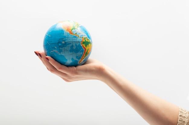 Globo pequeno em uma palma feminina. mundo em mãos humanas.