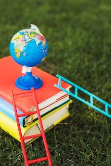 Globo pequeno, organizado em cima da pilha de livros