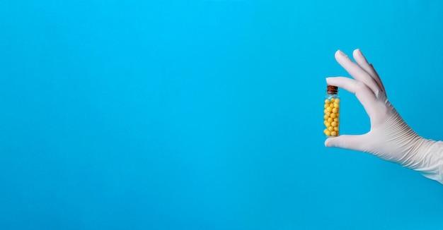 Glóbulos amarelos garrafa de vidro na mão enluvada. bandeira. copie o espaço
