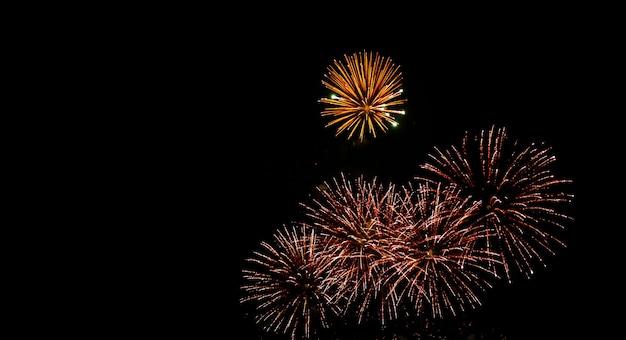 Glod e vermelho fogos de artifício brilham no céu da noite