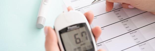 Glucômetro com resultados de teste de sangue na mão do paciente preenche os resultados no relatório diário