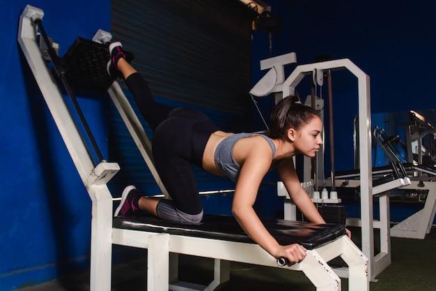 Glúteos de treinamento linda garota atlética com uma máquina na academia.