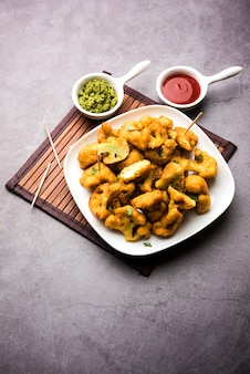 Gobi pakora ou phoolgobi pakoda feito com couve-flor fresca mergulhada em massa de grão de bico e depois frita em óleo. servido com ketchup de tomate e chutney de hortelã. foco seletivo