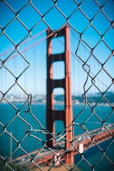 Golden gate bridge icônico através de uma cerca, san francisco.