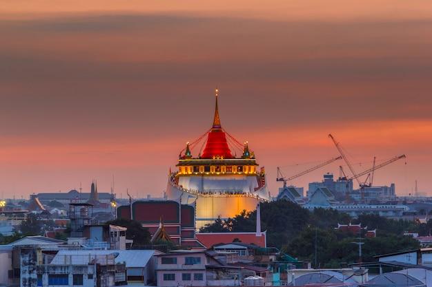 Golden mount temple fair, monte dourado templo com pano vermelho em bangkok ao anoitecer (wat sraket, tailândia)