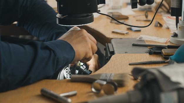 Goldsmith no trabalho. bancada de trabalho do joalheiro com diferentes ferramentas