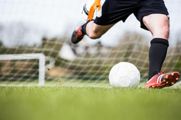 Goleiro chutando bola longe do gol