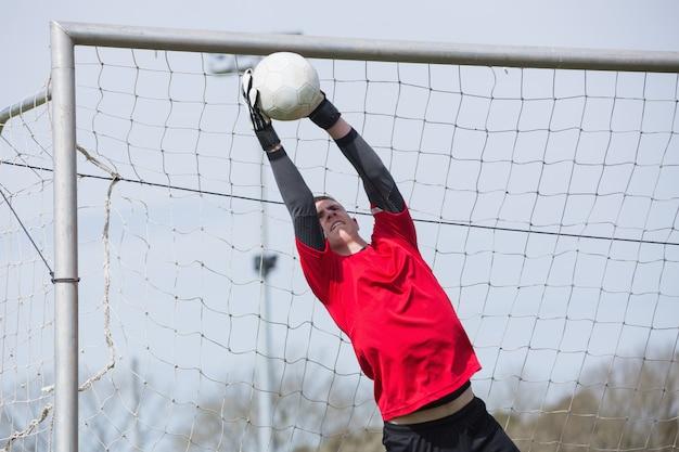 Goleiro em vermelho pulando para salvar um gol
