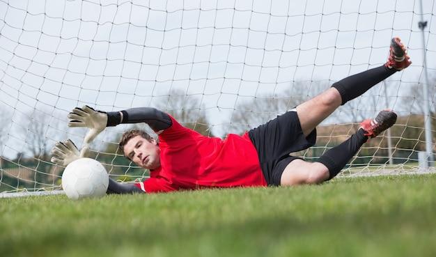 Goleiro em vermelho, salvando um gol durante um jogo
