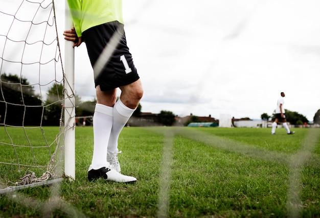 Goleiro masculino em pé pelo gol
