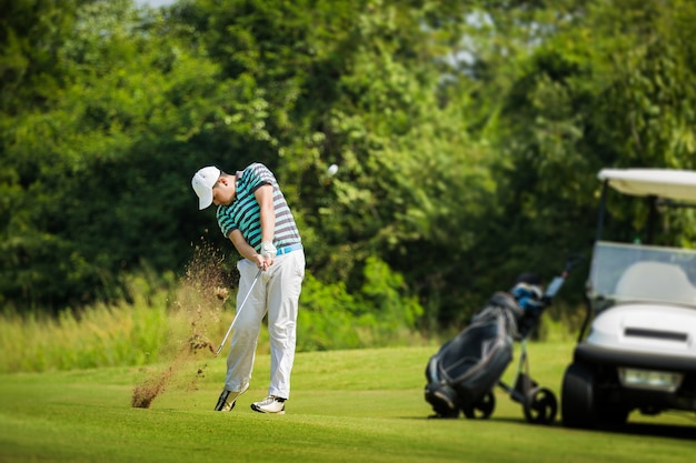 Golfer bater bola com força. a distribuição de grama o borrão de golfe