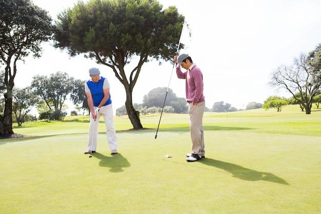 Golfista balançando seu clube com um amigo