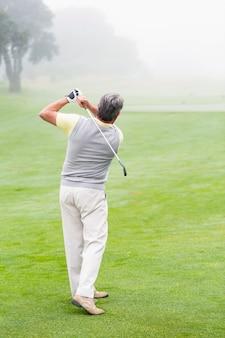 Golfista balançando seu clube no campo