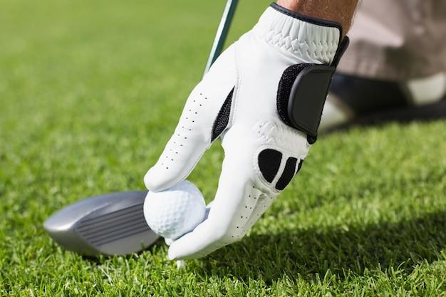 Golfista colocando bola de golfe no tee