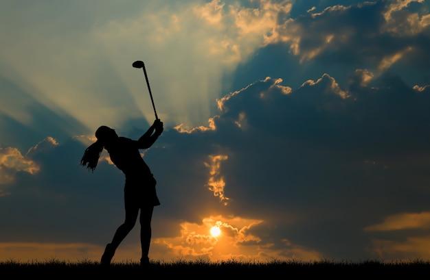 Golfista de silhueta jogando golfe durante o pôr do sol