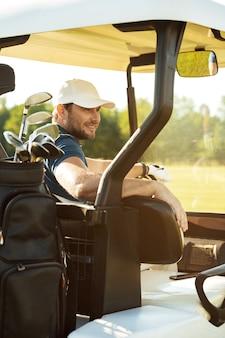 Golfista masculina sorridente, sentado em um carrinho de golfe