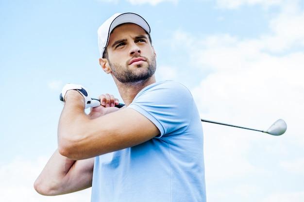 Golpe perfeito. vista de baixo ângulo de um jovem jogador de golfe balançando seu driver e olhando para longe com o céu azul como pano de fundo