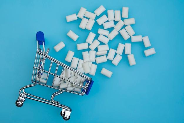 Goma de mascar no carrinho de compras. uma variedade de chiclete em um mini carrinho de compras. conceito de compras.