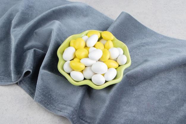 Gomas amarelas e brancas na toalha na superfície do mármore