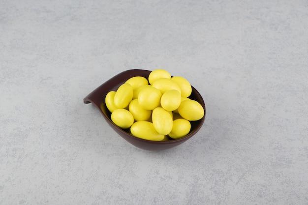 Gomas amarelas na tigela na superfície do mármore