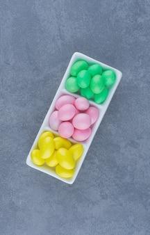 Gomas amarelas, verdes e rosa na placa, no fundo de mármore.
